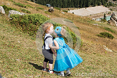 Baby boy and adorable child girl kissing  on grass. Summer green nature
