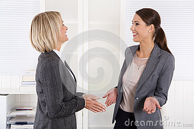 Two successful happy businesswoman talking together.