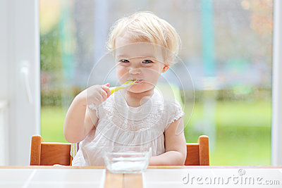 Cute baby girl eating yogurt from spoon