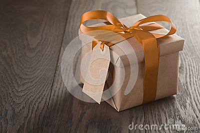 Rustic gift box with orange ribbon bow and empty tag