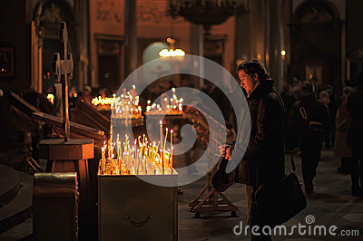People in the church and light candles