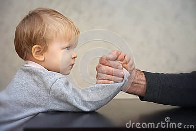 Father and kid arm wrestling competition