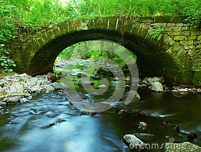 The old stony bridge of mountain stream in leaves forest, cold blurred water is running bellow.