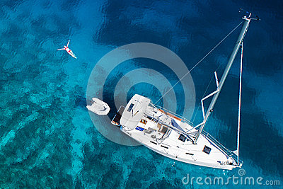 Amazing view to yacht, swimming woman and clear water in caribbean paradise