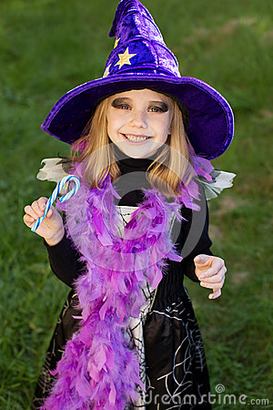 Little beautiful girl with halloween witch costume smiling and have colored candy