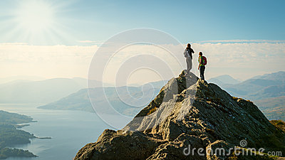 Female hikers on top of the mountain enjoying valley view