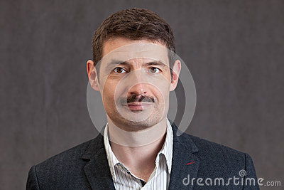 Passport photo of a smiling forties man with a short mustache