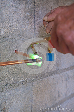 Plumber soldering copper pipe