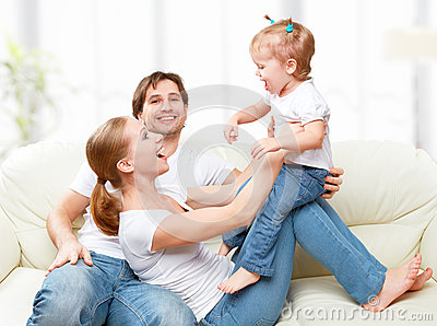 Happy family mother, father, child baby daughter at home on  sofa playing and laughing