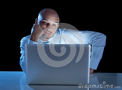 Overworked businessman working on computer laptop late night  exhausted