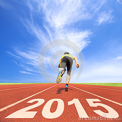 Happy new year 2015. young man running on track
