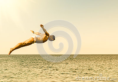 Cliff diver jumping in the sea against the sky at sunset