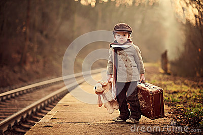 Adorable boy on a railway station, waiting for the train