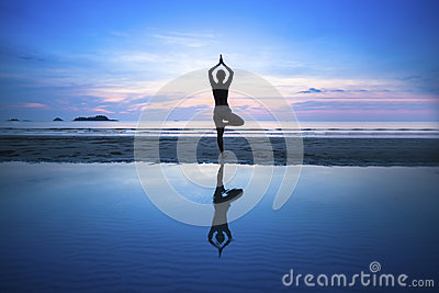 Young woman practicing yoga on beach at surrealistic sunset.