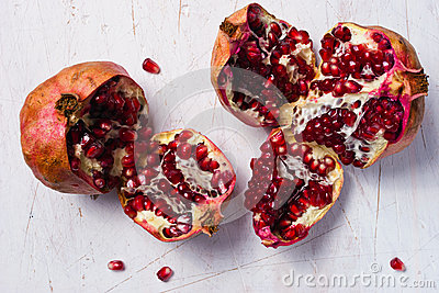 Two uncovered pomegranates on the white table