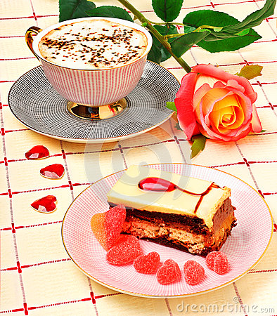 Cap of coffee, a rose and a cake on tablecloth