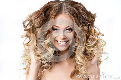 Portrait of beautiful young smiling girl with luxuriant hair curling.