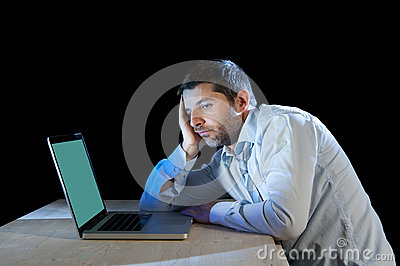 Young stressed businessman working on desk with computer laptop in frustration and depression