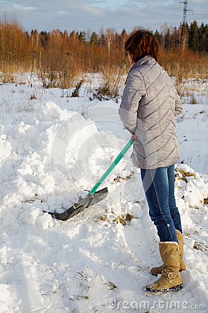 The woman cleans snow