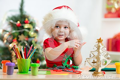 Child in Santa hat making christmas tree of
