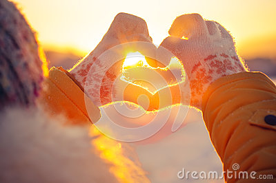 Woman hands in winter gloves Heart symbol shaped