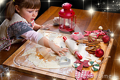 Little girl baking Christmas cookies cutting pastry