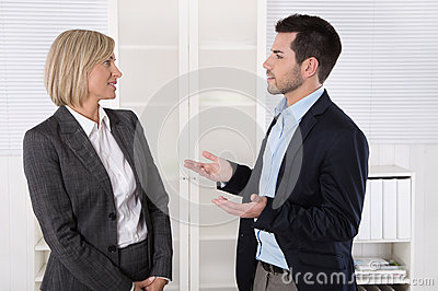 Two business people working in a team talking together in the of
