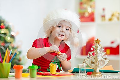 Kid in Santa hat making christmas tree of