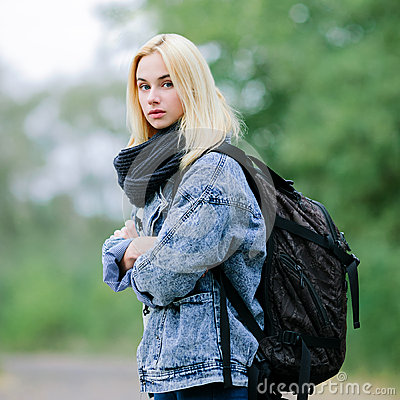 Outdoors portrait of a young beautiful blonde woman in jeans with a big old backpack
