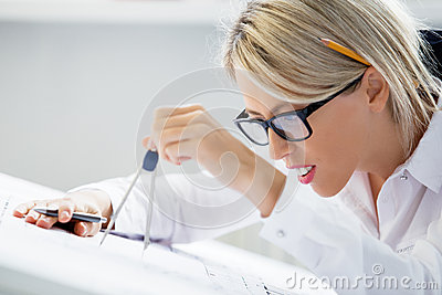 Female engineer working on blueprint with drawing compass