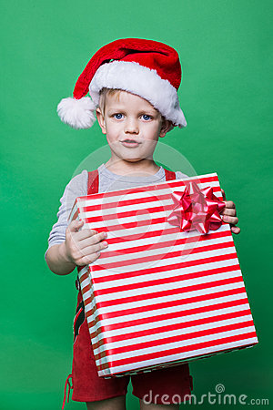 Christmas Elf holding big red gift box with ribbon. Santa Claus helper