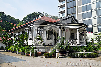 Traditional colonial house Singapore next to modern highrise building