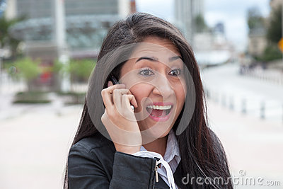 Cheering latin woman talking at phone in the city