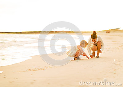 Mother and baby girl drawing on sand on beach