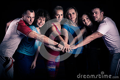 Teamwork concept.Fitness workout team motivation.Group of athletic healthy adults in gym giving group high five.United hands.