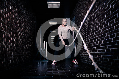 Fitness battling ropes at gym workout fitness exercise done by handsome good looking man. Crossfit battling ropes at gym workout