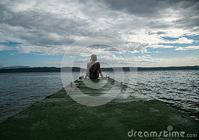 Depressed woman.Young girl depression,stress and problems,pain,female depressed.Young woman sitting on pier looking over horizon
