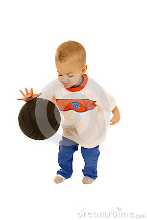 Cute two year old boy bouncing black basketball