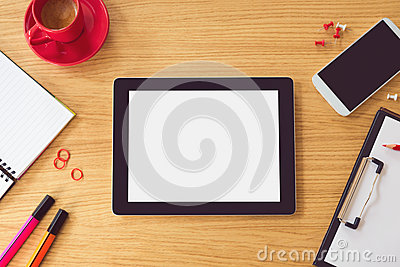 Tablet with blank white screen on wooden table. Office desk mock up. View from above