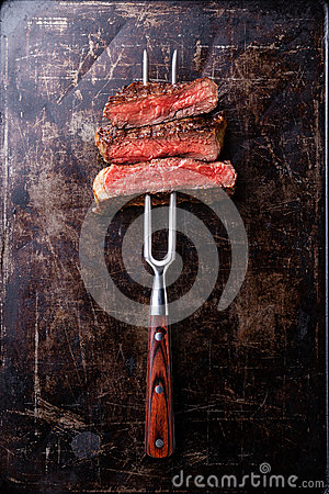 Slices of Rare beef steak on meat fork