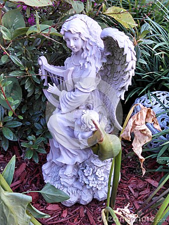 Angel playing harp in a garden