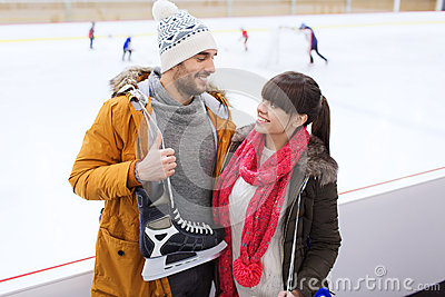 Happy couple with ice-skates on skating rink