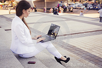 Beautiful brunette business woman in white suit with notebook on her lap, typing, working outdoors