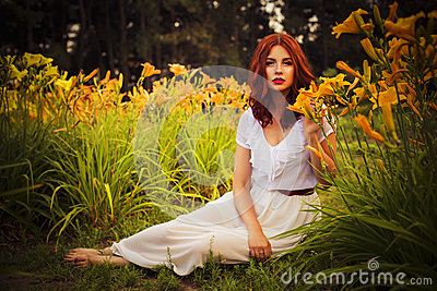 Brunette caucasian woman in white dress at the park in red and yellow flowers on a summer sunset holding flowers sitting on the gr