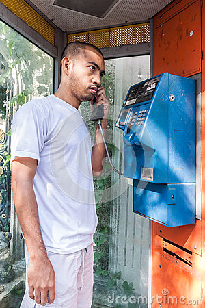 Seriously asian man using  payphone