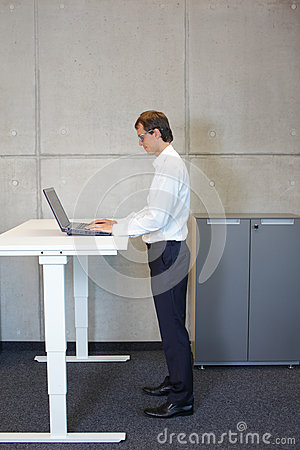 Business man with eyeglasses standing at  height adjustment table