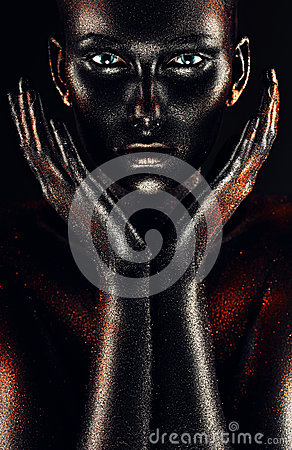 Woman in black paint with hands around cheeks