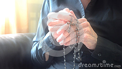 Divine light over hands of elder woman praying with rosary