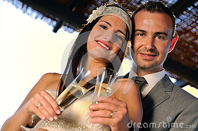 Groom and bride toasting smiling on a terrace looking ahead