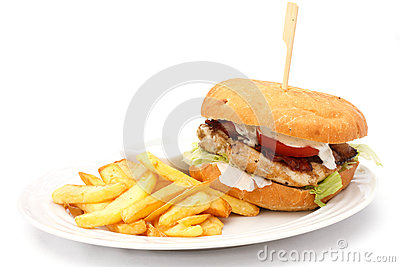 Grilled chicken burger with chips on white plate.